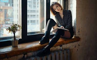 Girl model, reading book, at window