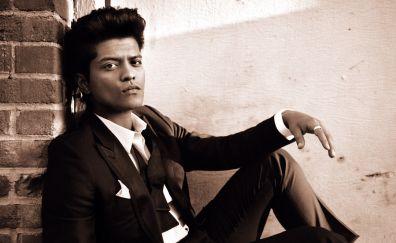 Singer Bruno Mars, sitting, sepia