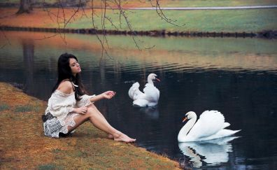 Girl and swans in river
