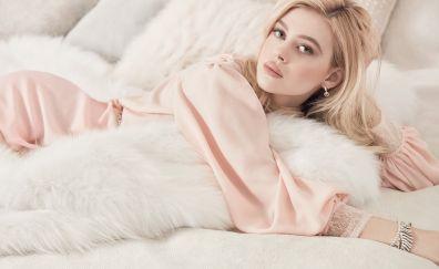 Nicola Peltz on bed, blonde actress