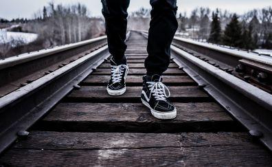 Sneakers, railway lines and legs