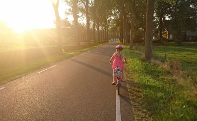 Girl riding bicycle, road, morning, sunlight