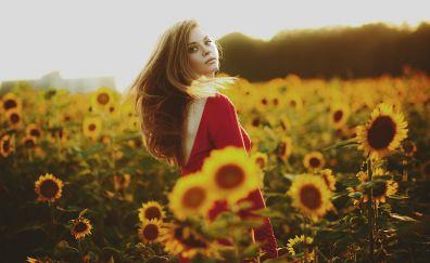 Cute girl in sunflower field