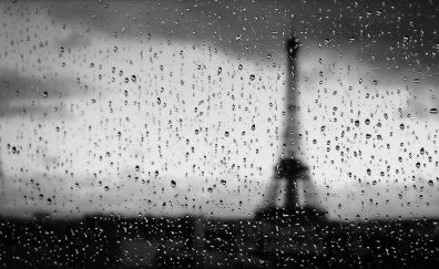 Eiffel tower of Paris through water drops window surface