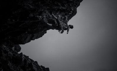 Monochrome rock climbing of man