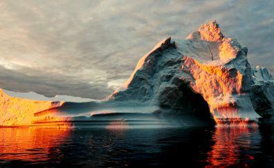 Iceberg, the ocean, golden sunlight